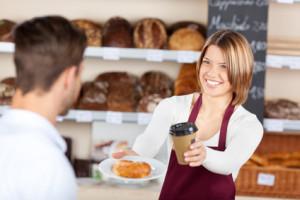 verkäuferin mit croissant und kaffeebecher